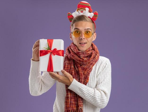 Beeindruckter junger hübscher kerl, der weihnachtsmann-stirnband und schal hält, die geschenkpackung betrachten kamera betrachten, die auf purpurrotem hintergrund lokalisiert wird