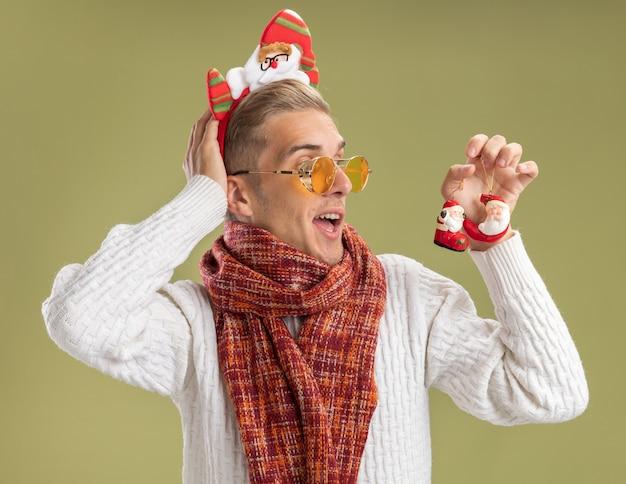 Beeindruckter junger hübscher kerl, der weihnachtsmann-stirnband und schal hält, die weihnachtsmann-weihnachtsverzierungen halten und betrachten, die hand hinter kopf lokalisiert auf olivgrünem hintergrund setzen