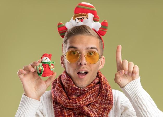 Beeindruckter junger hübscher kerl, der weihnachtsmann-stirnband und schal trägt, die kamera betrachten, die schneemann-weihnachtsverzierung hält, die kamera betrachtet, die lokal auf olivgrünem hintergrund zeigt