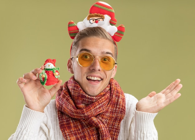 Beeindruckter junger hübscher kerl, der weihnachtsmann-stirnband und schal trägt, die kamera betrachten, die schneemann-weihnachtsverzierung hält, die leere hand lokalisiert auf olivgrünem hintergrund zeigt