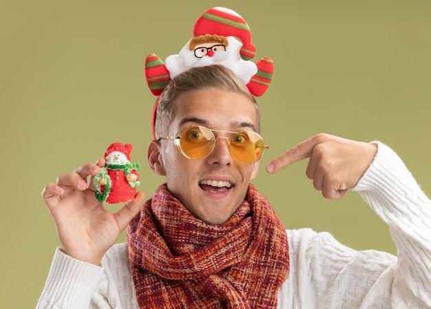 Beeindruckter junger hübscher kerl, der weihnachtsmann-stirnband und schal trägt, die kamera halten und auf schneemann-weihnachtsschmuck zeigen, der auf olivgrünem hintergrund lokalisiert ist