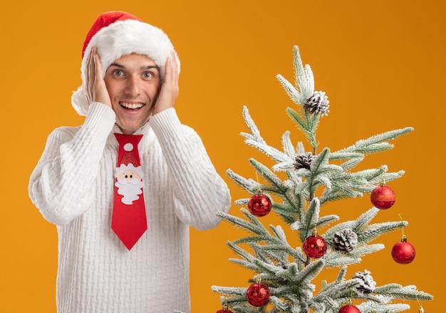 Beeindruckter junger hübscher kerl, der weihnachtsmütze und weihnachtsmannkrawatte trägt, die nahe verziertem weihnachtsbaum steht und hände auf kopf hält, der kamera lokalisiert auf orange hintergrund betrachtet