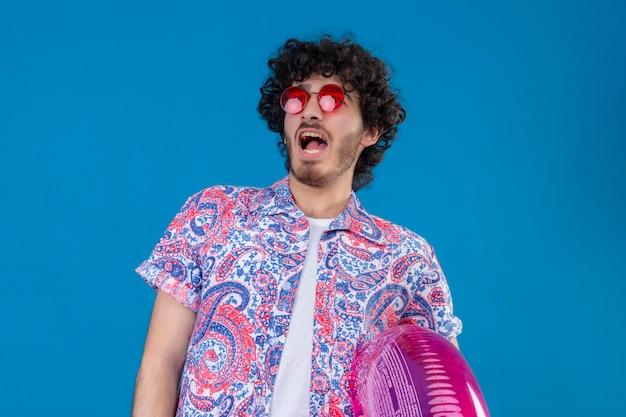 Beeindruckter junger hübscher lockiger mann, der sonnenbrillen hält, die schwimmring auf lokalisiertem blauem raum mit kopienraum halten