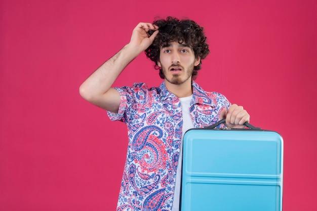 Beeindruckter junger hübscher lockiger reisender mann, der hand auf koffer legt und sein haar auf isoliertem rosa raum mit kopienraum berührt