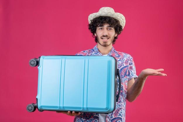 Beeindruckter junger hübscher lockiger reisender mann, der hut hält, der brieftasche und flugtickets und koffer hält und leere hand auf lokalisiertem rosa raum zeigt