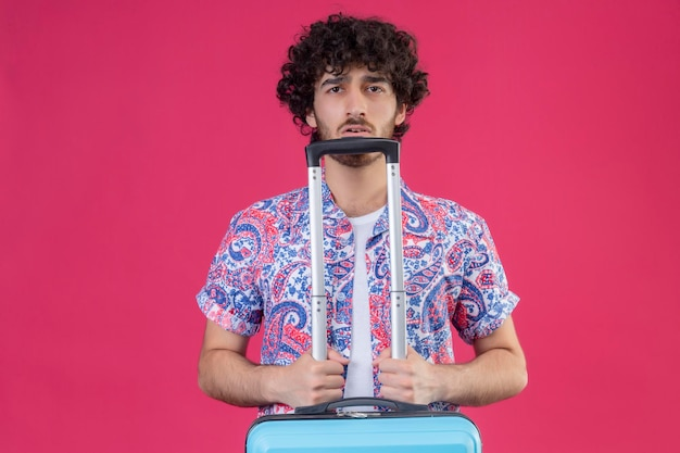 Beeindruckter junger hübscher lockiger reisender mann, der koffer auf lokalisiertem rosa raum mit kopienraum hält