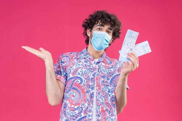 Beeindruckter junger hübscher lockiger reisender mann, der medizinische maske hält, die flugtickets hält, die leere hand auf lokalisiertem rosa raum zeigen