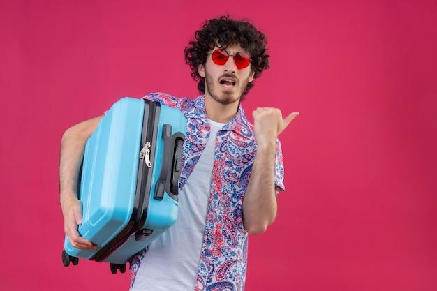 Beeindruckter junger hübscher lockiger reisender mann, der sonnenbrille hält, koffer hält und auf der rechten seite auf isolierten rosa raum mit kopienraum zeigt