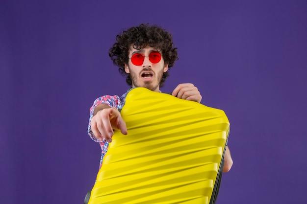 Beeindruckter junger hübscher lockiger reisender mann, der sonnenbrille hält, koffer hält und auf isolierten lila raum mit kopienraum zeigt