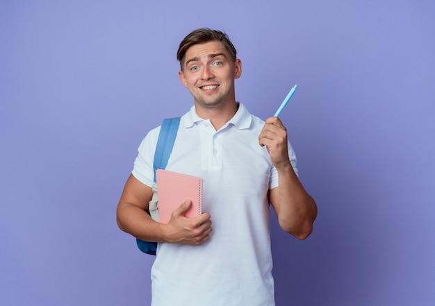 Beeindruckter junger hübscher männlicher student, der rückentasche hält, die notizbuch mit stift lokalisiert auf blauer wand hält