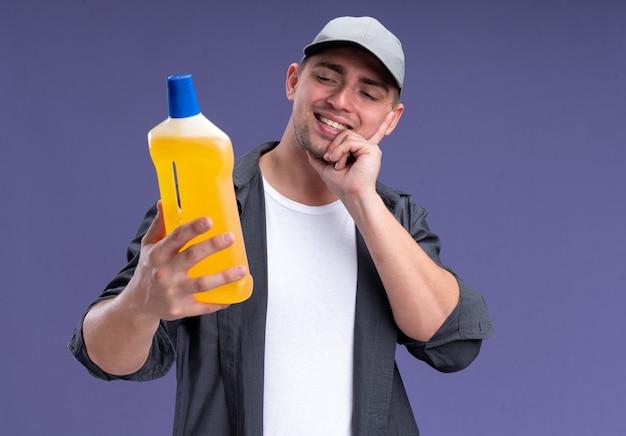 Beeindruckter junger hübscher reinigungsmann, der t-shirt und kappe hält und reinigungsmittel hält, das finger auf wange lokalisiert auf lila wand setzt