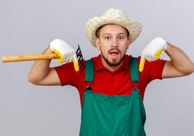 Beeindruckter junger hübscher slawischer gärtner in der uniform, die gartenhandschuhe und hut hält, der rechen hält, der lokal auf weiße wand zeigt