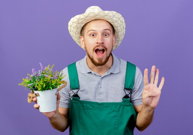 Beeindruckter junger hübscher slawischer gärtner in der uniform und im hut, der blumentopf hält, der leere hand lokalisiert auf lila wand zeigt