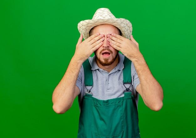 Beeindruckter junger hübscher slawischer gärtner in uniform und hut, der augen mit händen bedeckt
