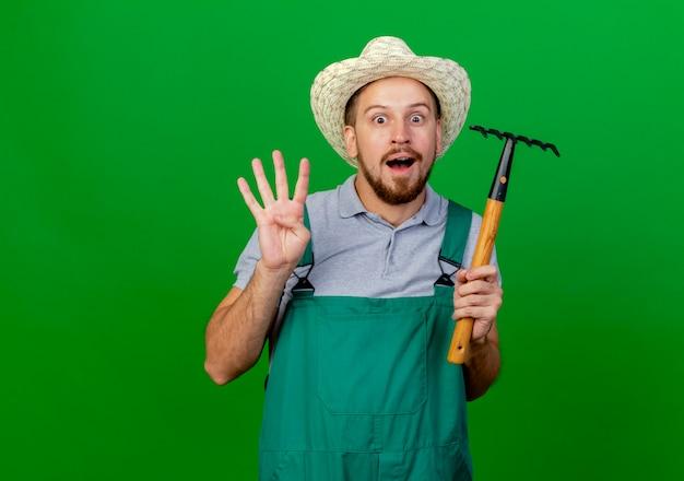 Beeindruckter junger hübscher slawischer gärtner in uniform und hut, der rechen hält, der vier mit der hand zeigt