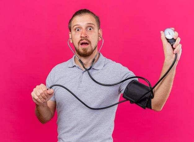 Beeindruckter junger hübscher slawischer kranker mann, der stethoskop trägt, das seinen druck mit blutdruckmessgerät misst, das front lokalisiert auf rosa wand betrachtet