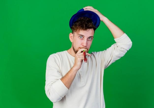 Beeindruckter junger hübscher slawischer mann, der partyhut aufbläst, der partygebläse bläst, das front lokal auf grüner wand mit kopienraum betrachtet