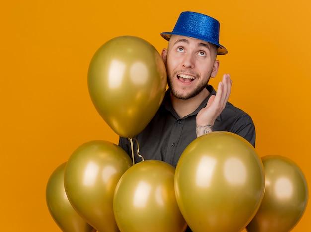 Beeindruckter junger hübscher slawischer partei-kerl, der parteihut trägt, der unter luftballons steht, die hand in der luft halten, die lokal auf orange hintergrund schaut