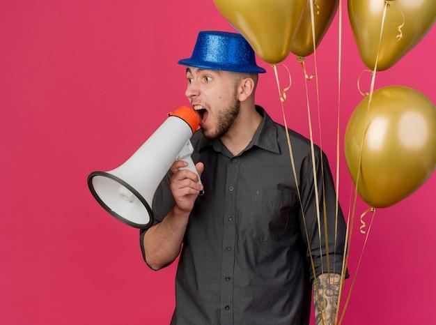 Beeindruckter junger hübscher slawischer party-typ, der partyhut hält, der ballone hält, die im lauten lautsprecher schreien, der seite lokal auf purpurrotem hintergrund betrachtet