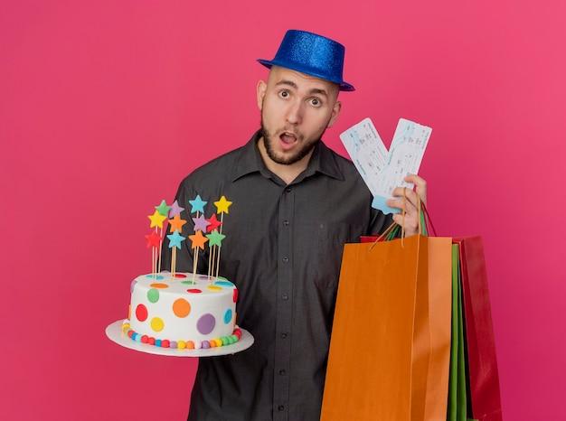 Beeindruckter junger hübscher slawischer party-typ, der partyhut hält, der geburtstagskuchen-flugtickets und papiertüten betrachtet, die kamera lokal auf purpurrotem hintergrund betrachten