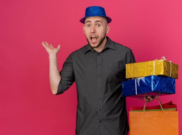 Beeindruckter junger hübscher slawischer party-typ, der partyhut hält, der geschenkverpackungen und papiertüten betrachtet kamera betrachtet, die leere hand lokalisiert auf purpurrotem hintergrund mit kopienraum zeigt