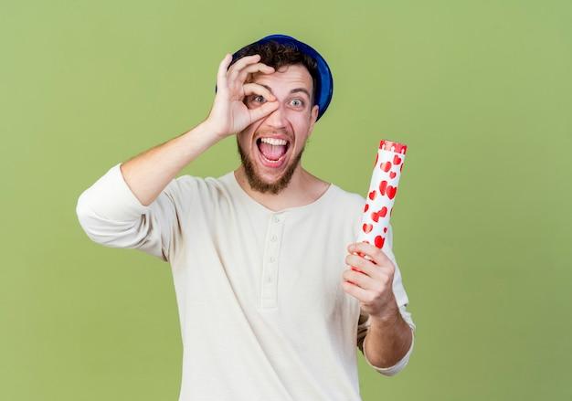 Beeindruckter junger hübscher slawischer party-typ, der partyhut hält, der konfetti-kanone hält, die kamera schaut blickgeste auf olivgrünem hintergrund mit kopienraum
