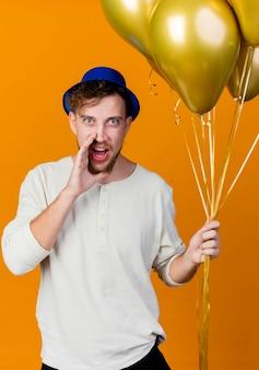 Beeindruckter junger hübscher slawischer party-typ, der partyhut hält, der luftballons hält, das frontflüstern lokalisiert auf orange wand betrachtet