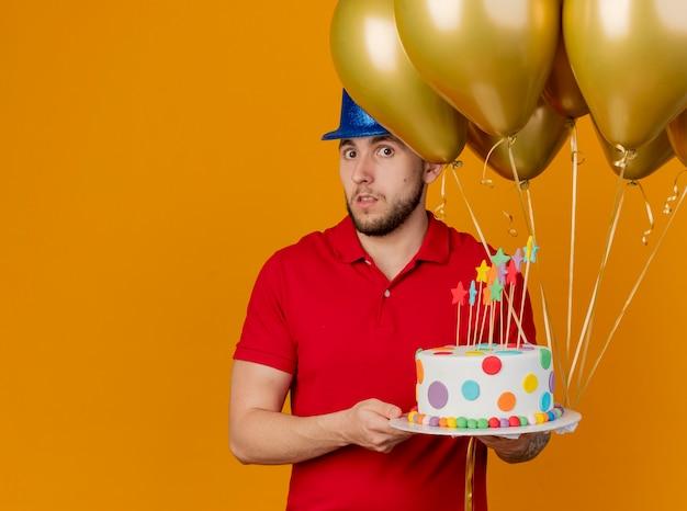Beeindruckter junger hübscher slawischer party-typ, der partyhut hält, der luftballons und geburtstagstorte hält und kamera lokalisiert auf orange hintergrund mit kopienraum betrachtet