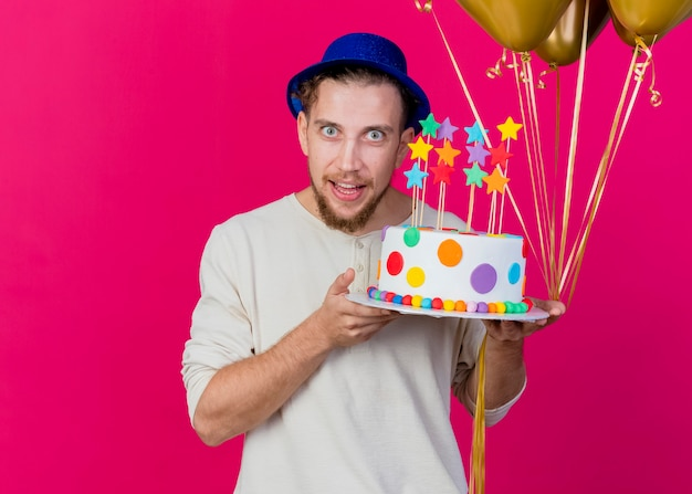 Beeindruckter junger hübscher slawischer party-typ, der partyhut hält, der luftballons und geburtstagstorte mit sternen hält, die kamera lokal auf purpurrotem hintergrund mit kopienraum betrachten