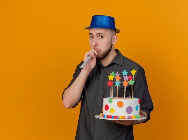 Beeindruckter junger hübscher slawischer party-typ, der partyhut mit blick auf die front hält, die geburtstagstorte bläst party-gebläse lokalisiert auf orange wand mit kopienraum