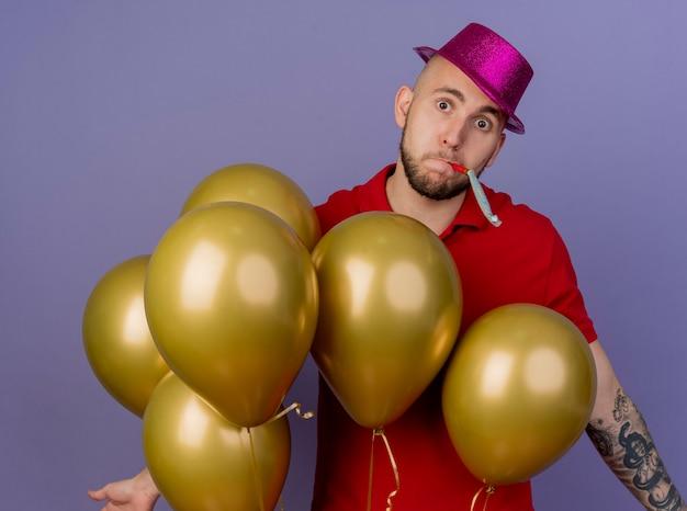 Beeindruckter junger hübscher slawischer party-typ, der partyhut trägt, der hinter luftballons steht und kamera betrachtet, die leere hände mit partygebläse im mund lokalisiert auf lila hintergrund zeigt