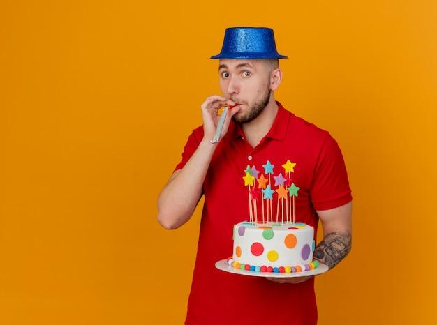 Beeindruckter junger hübscher slawischer party-typ, der partyhut trägt, der kamera betrachtet, die geburtstagstorte mit partygebläse im mund lokalisiert auf orange hintergrund mit kopienraum hält