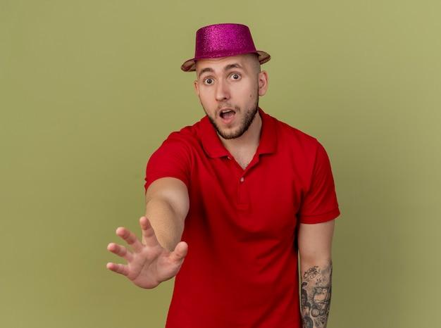 Beeindruckter junger hübscher slawischer party-typ, der partyhut trägt, der kamera betrachtet, die hand in richtung kamera streckt, lokalisiert auf olivgrünem hintergrund mit kopienraum
