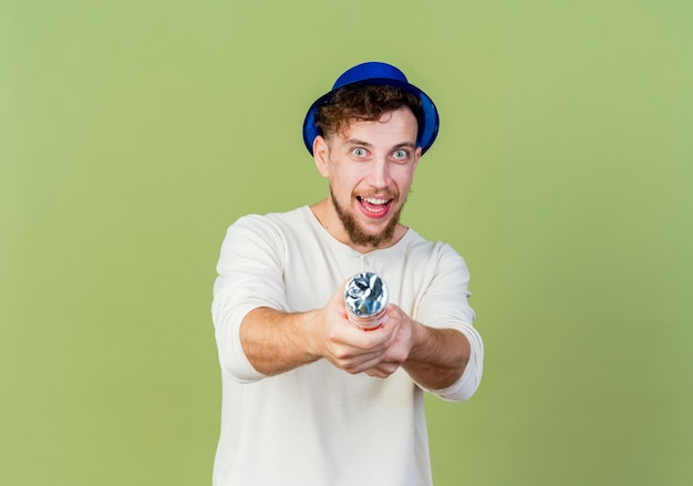 Beeindruckter junger hübscher slawischer party-typ, der partyhut trägt, der kamera betrachtet, die konfettikanone in richtung kamera streckt, lokalisiert auf olivgrünem hintergrund mit kopienraum