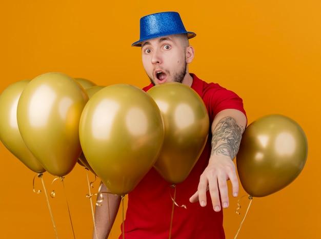 Beeindruckter junger hübscher slawischer party-typ, der partyhut trägt, der unter luftballons steht, die kamera betrachten, die hand in richtung kamera streicht, die auf orange hintergrund lokalisiert wird