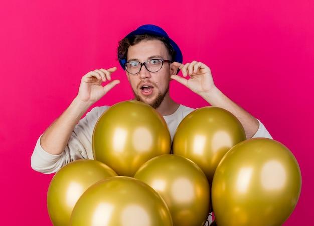 Beeindruckter junger hübscher slawischer party-typ, der partyhut und brille trägt, die hinter luftballons stehen und kamera betrachten, die kleine menge geste lokalisiert auf purpurrotem hintergrund tut