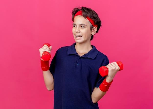 Beeindruckter junger hübscher sportlicher junge, der stirnband und armbänder mit zahnspangen hält, die hanteln halten, die seite lokalisiert auf rosa wand mit kopienraum betrachten