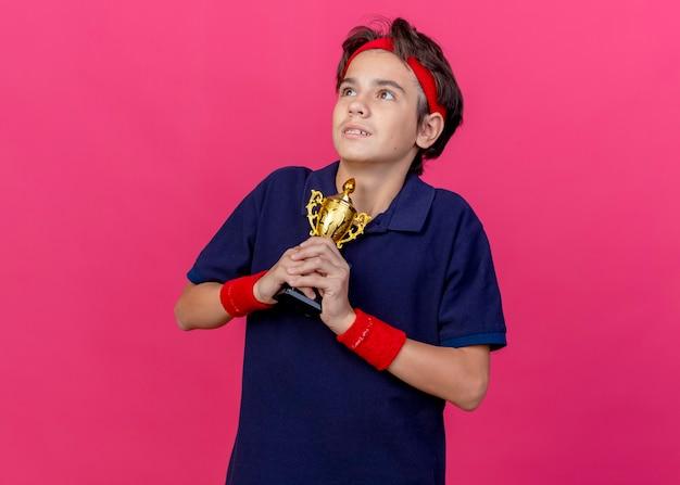 Beeindruckter junger hübscher sportlicher junge, der stirnband und armbänder mit zahnspangen hält, die siegerpokal halten, die seite betrachten, die auf purpurroter wand mit kopienraum lokalisiert wird