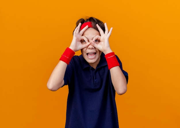 Beeindruckter junger hübscher sportlicher junge, der stirnband und armbänder mit zahnspangen trägt, die kamera betrachten blick geste unter verwendung der hände als fernglas lokalisiert auf orange hintergrund mit kopienraum