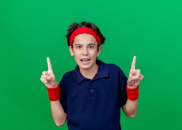 Beeindruckter junger hübscher sportlicher junge, der stirnband und armbänder mit zahnspangen trägt, die kamera betrachten, die lokal auf grünem hintergrund zeigt