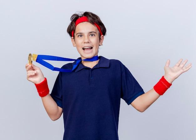 Beeindruckter junger hübscher sportlicher junge, der stirnband und armbänder mit zahnspangen und medaille um hals hält, die medaille hält, die leere hand lokalisiert auf weißer wand zeigt