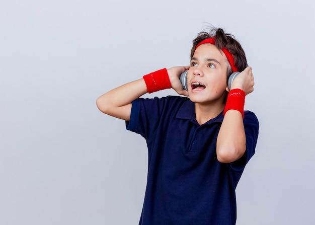 Beeindruckter junger hübscher sportlicher junge, der stirnband und armbänder und kopfhörer mit zahnspangen trägt, die seitliche berührende kopfhörer lokalisiert auf weißem hintergrund mit kopienraum betrachten