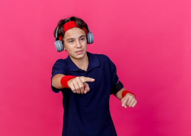 Beeindruckter junger hübscher sportlicher junge, der stirnband und armbänder und kopfhörer-telefonarmband mit zahnspangen trägt, die gerade lokal auf purpurroter wand mit kopienraum suchen und zeigen