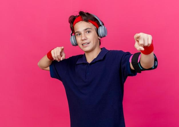 Beeindruckter junger hübscher sportlicher junge, der stirnband und armbänder und kopfhörer-telefonarmband mit zahnspangen trägt, die lokal auf purpurrote wand schauen und zeigen