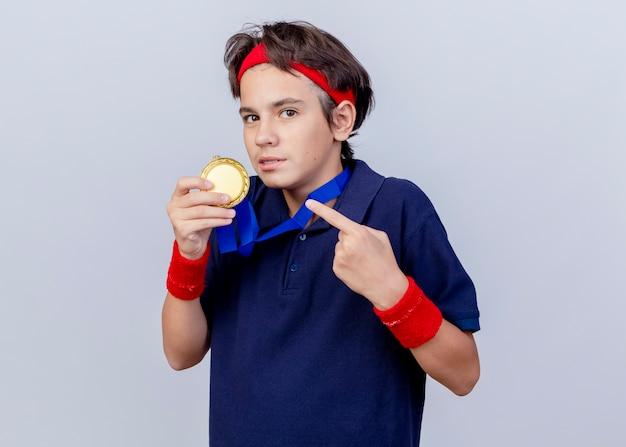 Beeindruckter junger hübscher sportlicher junge mit medaille um den hals, hält und zeigt auf medaille