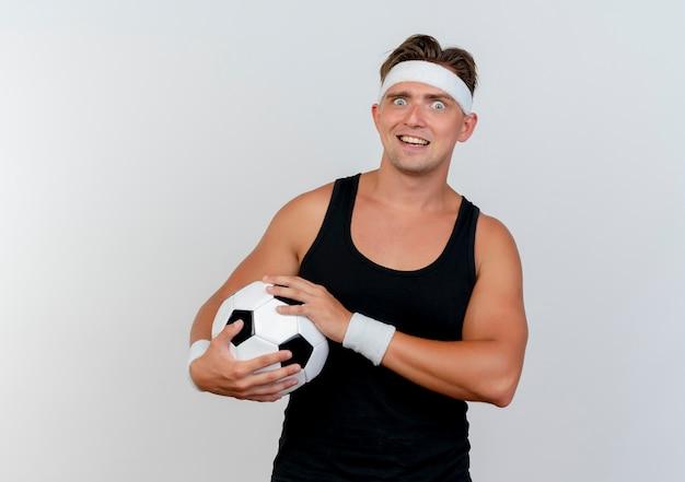 Beeindruckter junger hübscher sportlicher mann, der stirnband und armbänder hält, die fußball lokalisiert auf weiß halten