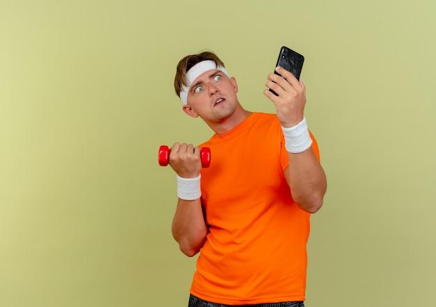 Beeindruckter junger hübscher sportlicher mann, der stirnband und armbänder hält, die handy und hantel halten, die telefon lokalisiert auf olivgrün betrachten