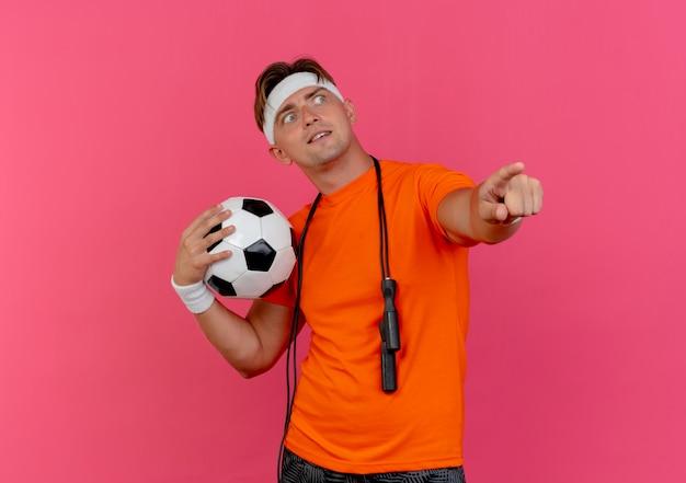 Beeindruckter junger hübscher sportlicher mann, der stirnband und armbänder mit springseil um den hals trägt, der fußball zeigt und auf seite lokalisiert auf rosa betrachtet