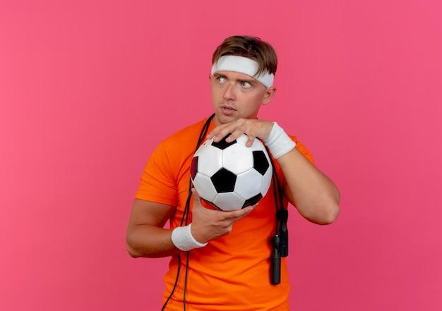 Beeindruckter junger hübscher sportlicher mann, der stirnband und armbänder mit springseil um hals hält, der fußball betrachtet seite betrachtet auf rosa lokalisiert