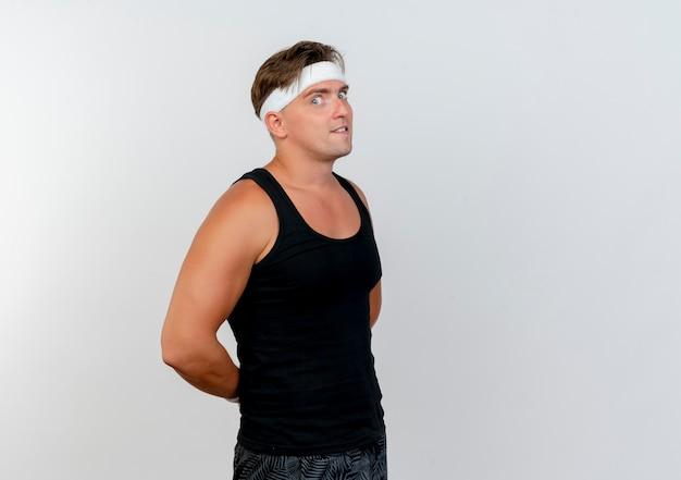 Beeindruckter junger hübscher sportlicher mann, der stirnband und armbänder trägt, die in der profilansicht stehen und hände hinter dem rücken lokalisiert auf weiß setzen